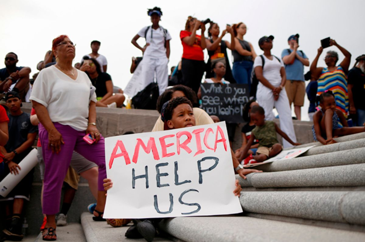 Kerron Stewart, 10, sits with demonstrators on the steps of the Louisiana State Capitol building in Baton Rouge, Louisiana, July 10, 2016. (Reuters/Shannon Stapleton)