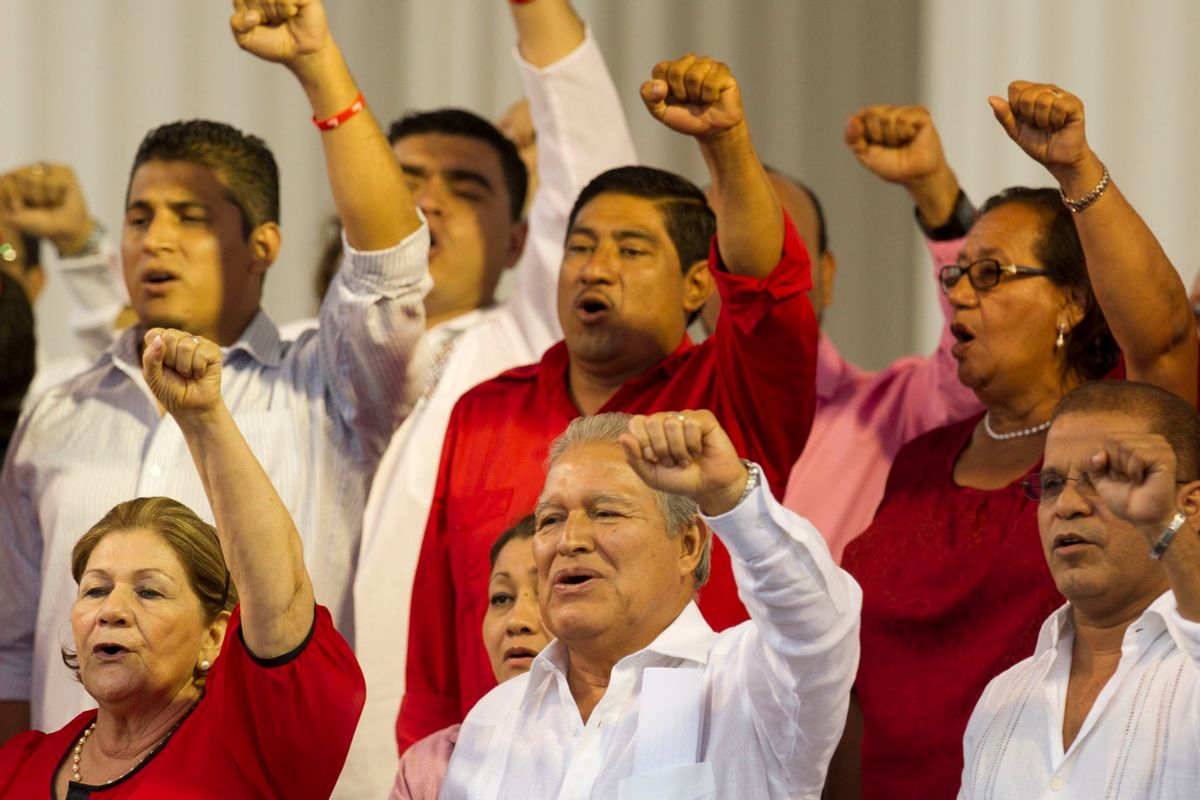 """FILE - In this June 1, 2014 file photo, El Salvador's President Salvador Sanchez Ceren sings the Farabundo Marti National Liberation Front anthem during a rally with party supporters after his swearing-in ceremony in San Salvador, El Salvador. Sanchez Ceren says he has begun talks with political parties on a new """"national reconciliation"""" law after the Supreme Court overturned an amnesty covering crimes committed during the 1980-1992 civil war. (AP Photo/Moises Castillo, File) (AP)"""