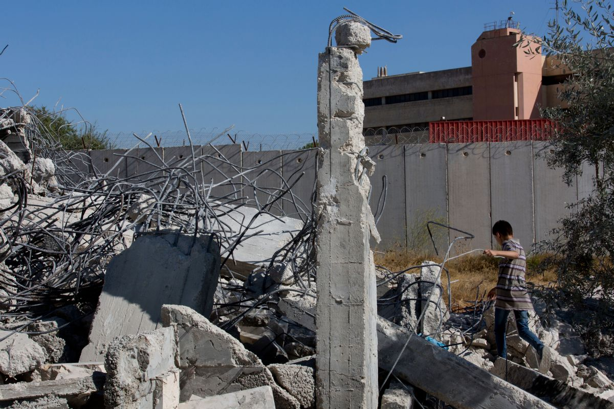 A Palestinian boy walks over the rubble of a house that overlooks the Israeli separation barrier, background, and was demolished by the Israeli army, in the West Bank village of Qalandia, near Ramallah, Tuesday, July 26, 2016.  (AP)