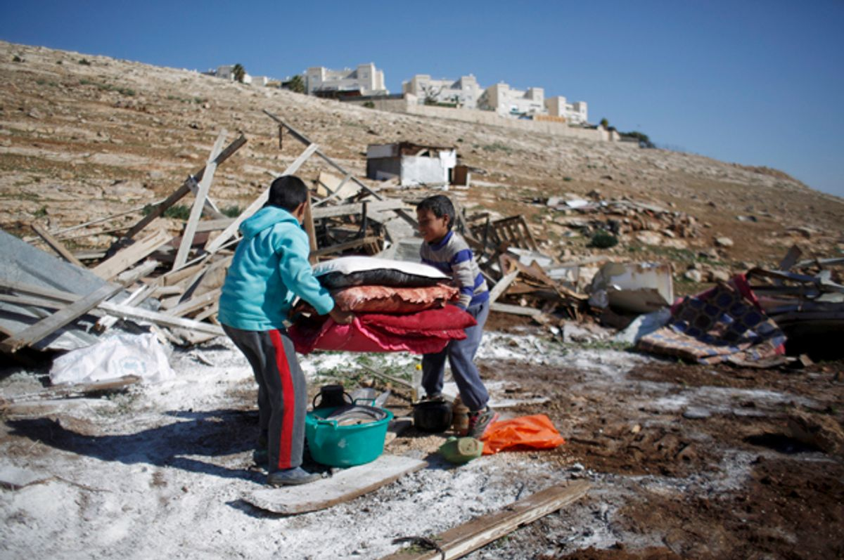 Palestinian boys carry their belongings after the Israeli army demolished their shanty, near the Israeli West Bank settlement of Maale Adumim, January 6, 2016.   (Reuters/Mohamad Torokman)