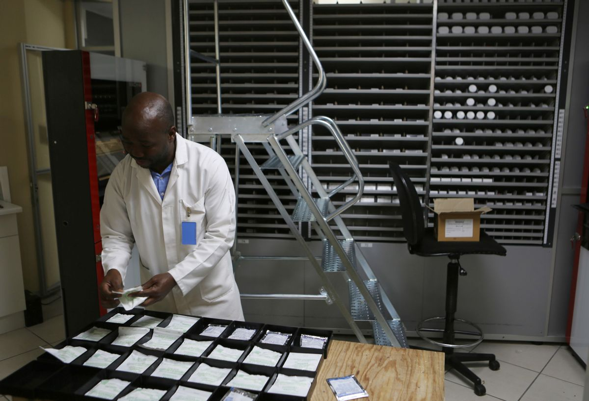 In this photo taken Friday July 15, 2016, a pharmacist makes up packets of drugs at the Helen Joseph Hospital in Johannesburg. In the largely black Johannesburg community of Alexandra, one project is trying to make drug delivery as convenient as withdrawing cash. What looks like a row of ATM machines has been installed in a shopping center, ready for an official rollout later this year. People will be able to walk up, insert their medical registration or speak via a video monitor with a pharmacy worker, select their prescription and pick up the drugs that pop out. (AP Photo/Denis Farrell) (AP)