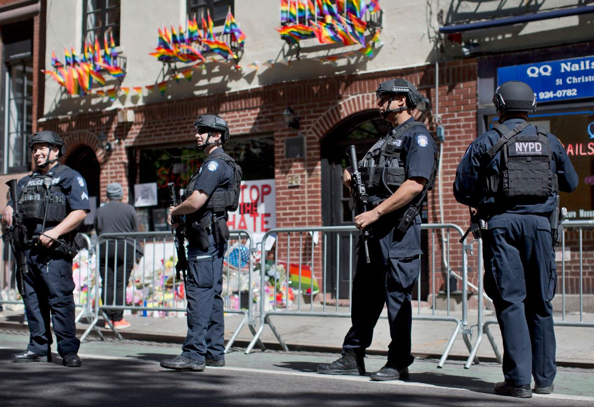 FILE - In this June 14, 2016 file photo, armed police officers stand guard outside the historic Stonewall Inn in New York as people congregate to pay their respects for the the victims and survivors of the Orlando nightclub shooting. The officers are heavily armed and equipped, in a manner typical of the NYPD's counterterrorism unit and Emergency Service Unit - the NYPD's equivalent of SWAT officers. But the NYPD plans to distribute 20,000 helmets and 6,000 vests before the end of the year to uniformed patrol officers to protect them better during combat with rampaging shooters (AP Photo/Mary Altaffer, File) (AP)