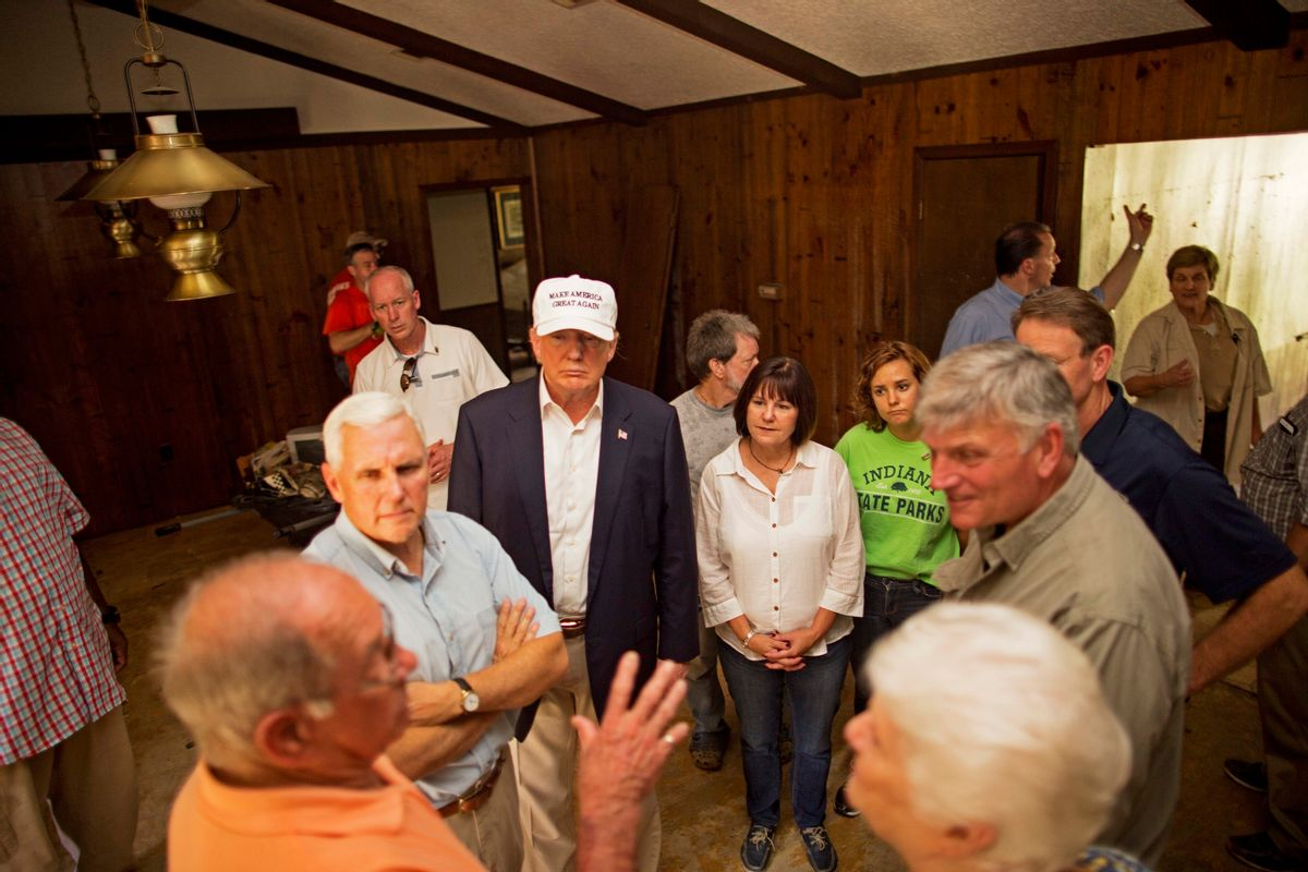 Republican presidential candidate Donald Trump, center, and his running mate, Indiana Gov. Mike Pence, listens to flood victims Jimmy and Olive Gordan during a tour of their flood damaged home in Denham Springs, La.,  (AP)