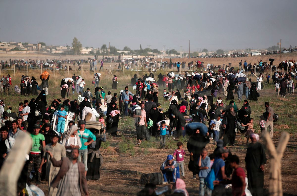 FILE - In this June 14, 2015 file photo taken from the Turkish side of the border between Turkey and Syria, in Akcakale, Sanliurfa province, southeastern Turkey, thousands of Syrian refugees walk in order to cross into Turkey. After a slow start, it appears increasingly likely that the Obama administration will hit its goal of admitting 10,000 Syrian refugees into the United States before the end of September. (AP Photo/Lefteris Pitarakis, File) (AP)