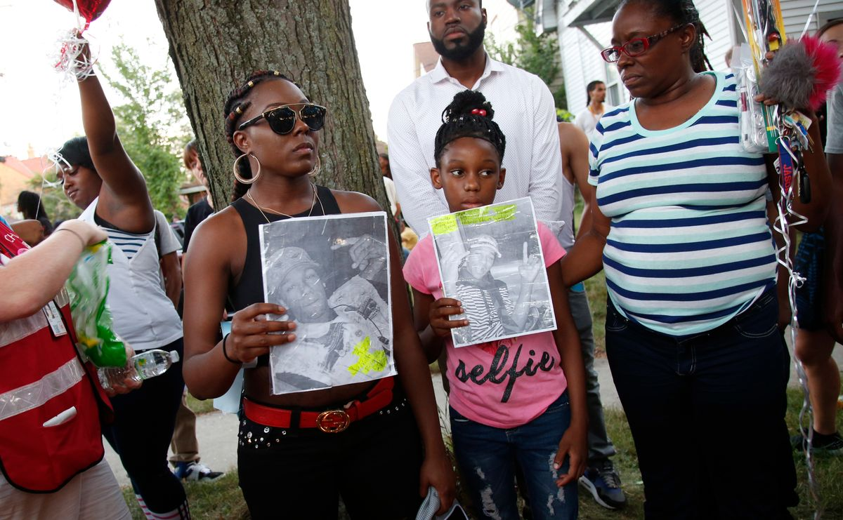 Family members of Sylville Smith gather where he was shot and killed by Milwaukee police in Milwaukee, Sunday, Aug. 14, 2016. Police in Milwaukee say a black man whose killing by police touched off arson and rock-throwing was shot by a black officer after turning toward him with a gun in his hand. Wisconsin's governor, meanwhile, has put the National Guard on standby in case of more violence Sunday night. (AP Photo/Jeffrey Phelps) (AP)