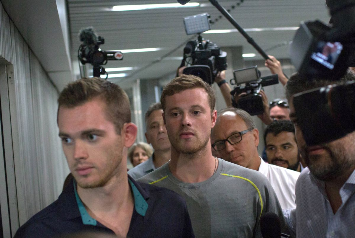 Journalists surround American Olympic swimmers Gunnar Bentz, left, and Jack Conger, center, as they leave the police station at Rio International airport early Thursday Aug. 18, 2016. The two were taken off their flight from Brazil to the U.S. on Wednesday by local authorities amid an investigation into a reported robbery targeting Ryan Lochte and his teammates. According to their lawyer they will not be allowed to leave Brazil until they provide testimony about the robbery. (AP Photo/Mauro Pimentel) (AP)