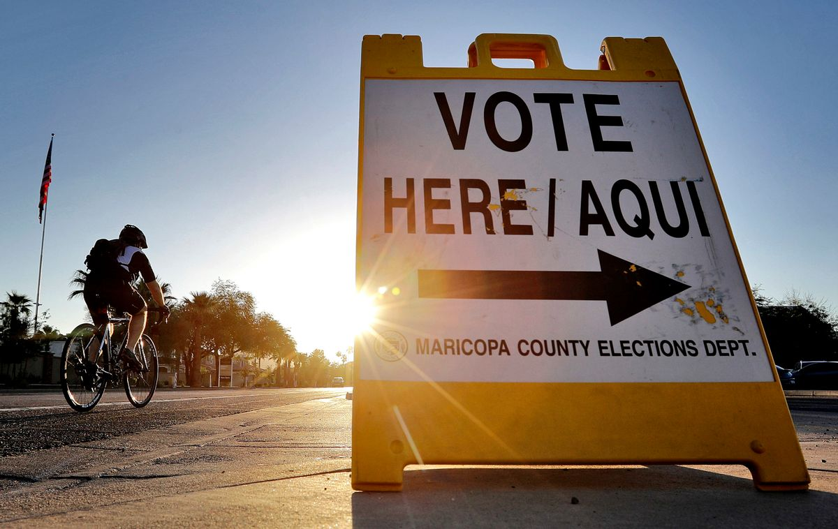 FILE - In this Aug. 30, 2016 file photo, a cyclist rides past a sign directing voters to a primary election voting station early, in Phoenix. Early voting kicks off next week in North Carolina, the first in a two-month run of voting through key swing states where non-whites and young adults could give one of the presidential campaigns a decisive advantage before Election Day.   (AP Photo/Matt York, File) (AP Photo/Matt York, File)
