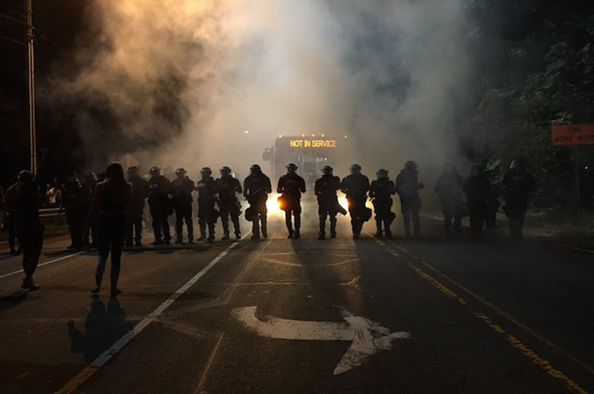 Police in riot gear use teargas to disperse protesters after police killed a disabled black man in Charlotte, North Carolina on Tuesday, September 20, 2016  (Adam Rhew/Charlotte magazine)