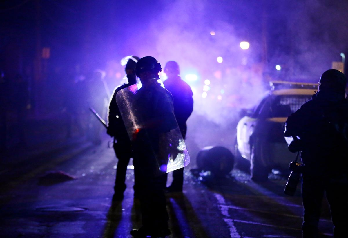 FILE - In this Nov. 25, 2014 file photo, police officers watch protesters as smoke fills the streets in Ferguson, Mo. Nearly two years after the fatal police shooting of 18-year-old Michael Brown put Ferguson in the national spotlight, city leaders are working to fill more than a dozen vacancies in the Missouri town's police department.  Mayor James Knowles III said Wednesday, Aug. 31, 2016, that finding qualified applicants has been tough and that diversity continues to be a goal. (AP Photo/Charlie Riedel, File) (AP)