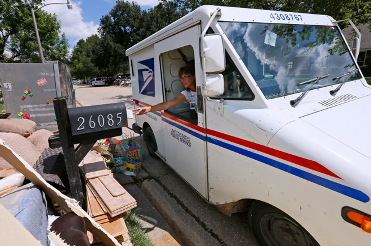 A United States Postal Service worker delivers mail to a flood damaged neighborhood in Denham Springs, Louisiana, August 23, 2016.   (Reuters/Jonathan Bachman)