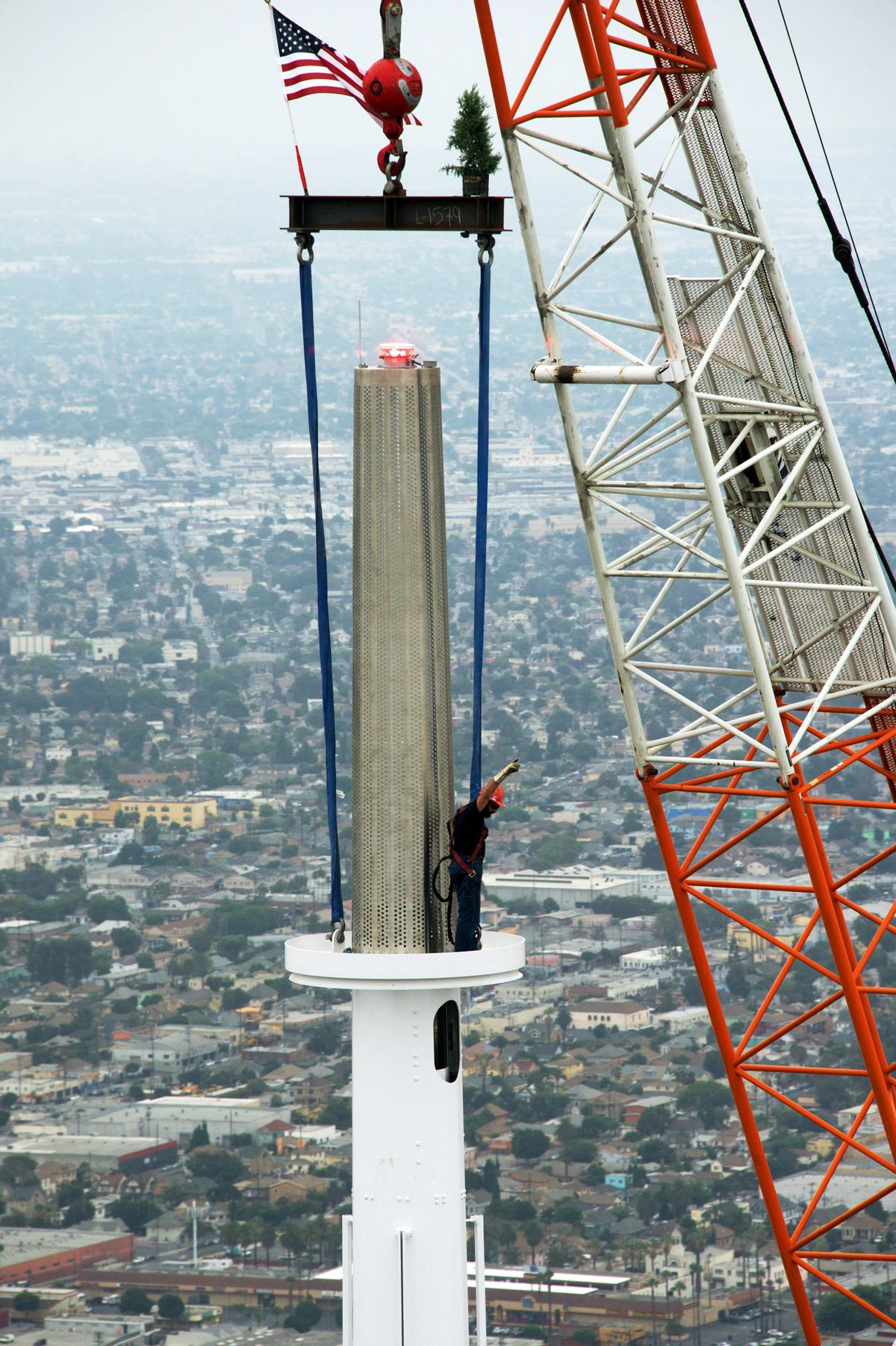 In this photo provided by the Wilshire Grand Center, a worker signals as a crane hoists a beacon into place atop a 160-foot spire on the Wilshire Grand Tower early Saturday, Sept. 3, 2016, in downtown Los Angeles. The 10-ton spire makes the structure the tallest building west of the Mississippi River. The $1 billion hotel and office complex is scheduled to open next March. (Gary Leonard/Wilshire Grand Center via AP) (AP)