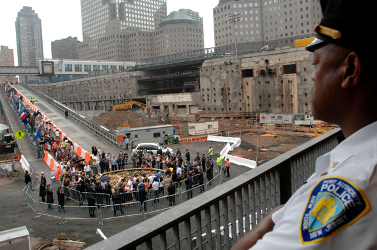 A Port Authority police officer watches the ceremony as victims' families walk down the ramp to place flowers in the reflecting pool during the ceremony on Sept. 11, 2007.   (AP/Susan Watts)