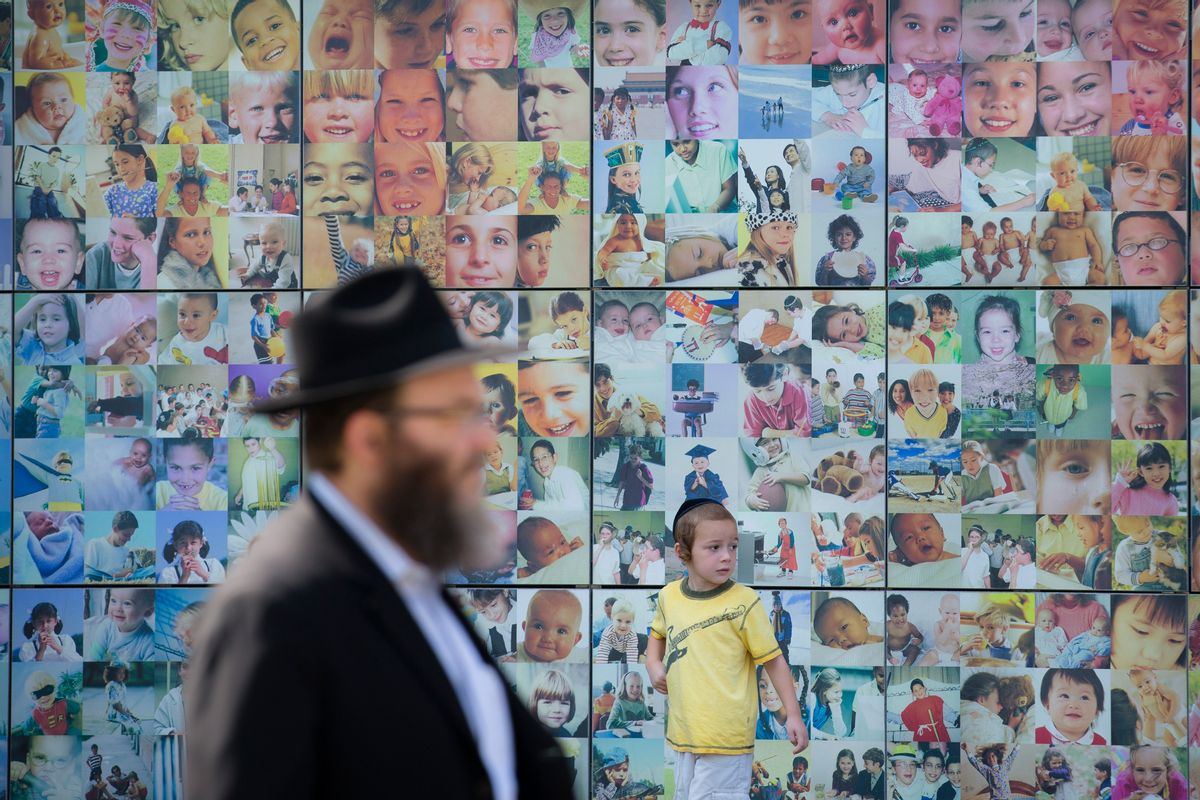 An Orthodox Jewish child walks alongside a collage wall at the Jewish Children's Museum, Monday, Aug. 11, 2014, in the Brooklyn borough of New York. The museum is the largest Jewish-themed children's museum in the United States. (AP Photo/John Minchillo) (AP)