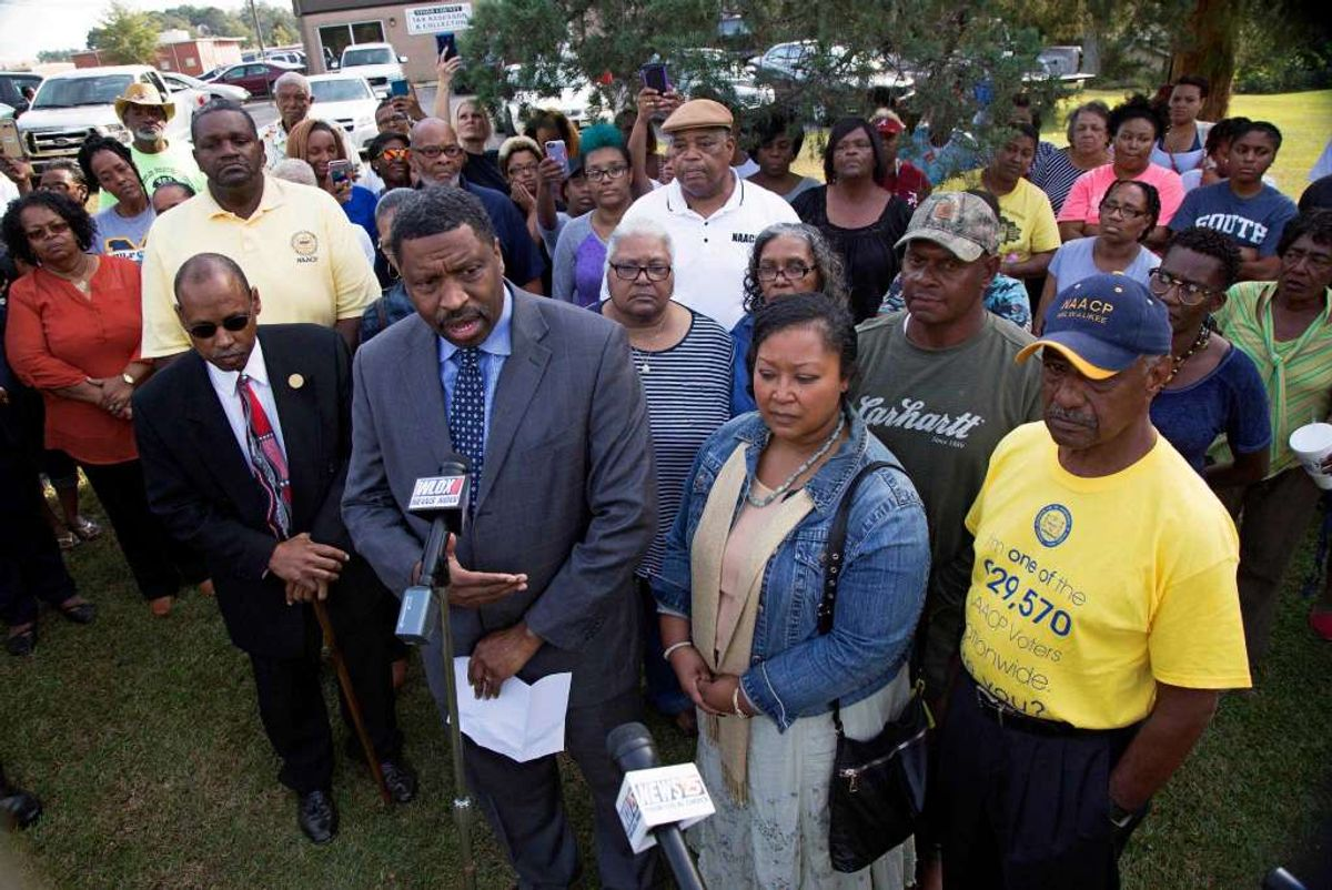 Derrick Johnson, left, president of the Mississippi NAACP, center left, talks to the media on behalf of Stacey Payton, center right, and Hollis Payton, behind his wife Stacey, in front of the Stone County Courthouse in Wiggins, Miss., Monday, Oct. 24, 2016. Johnson is demanding a federal investigation after the parents said four white students put a noose around their son's neck at school. (Max Becherer, AP)