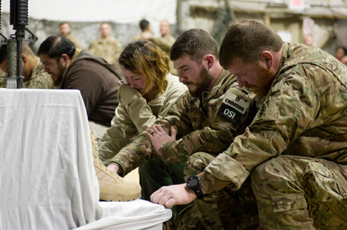 U.S. service members pay their respects during a memorial ceremony for six Airmen killed in a suicide attack, at Bagram Air Field, Afghanistan   (AP/Tech. Sgt. Robert Cloys)