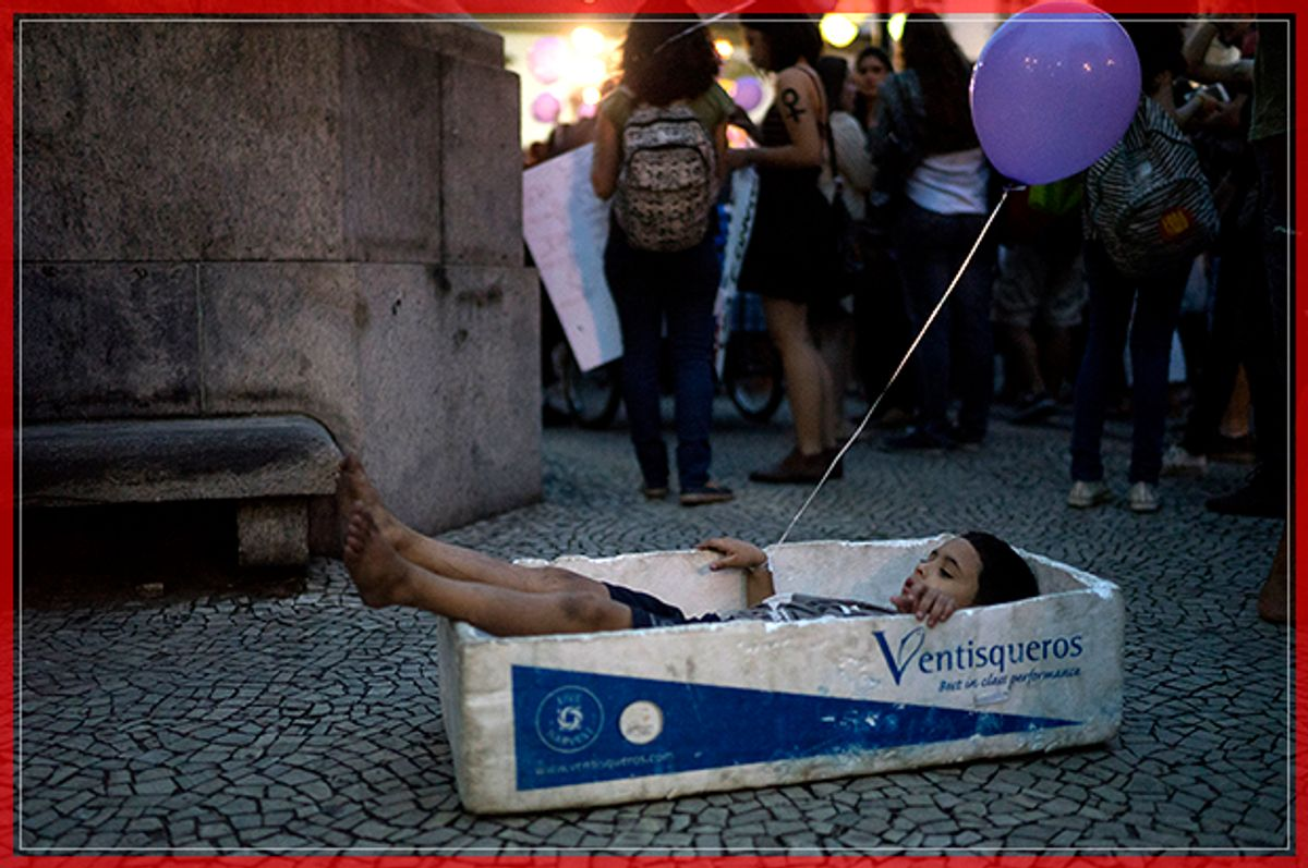 A boy plays with a foam box that is used to carry fish, during a demonstration against gender violence in Rio de Janeiro, Brazil, Tuesday, Oct. 25, 2016. Women in Brazil organized protests condemning violence against women following the recent brutal gang rape of a woman on the outskirts of Rio de Janeiro by suspected drug dealers. The boy played with the box as his street vendor father sold water during the demonstration. (AP Photo/Leo Correa) (AP)