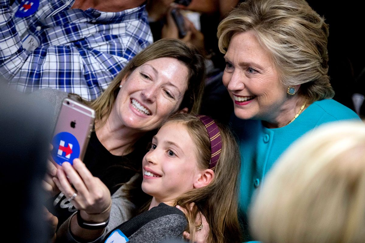 Democratic presidential candidate Hillary Clinton takes a photograph with supporters at a campaign office in Seattle, Friday, Oct. 14, 2016. (AP)