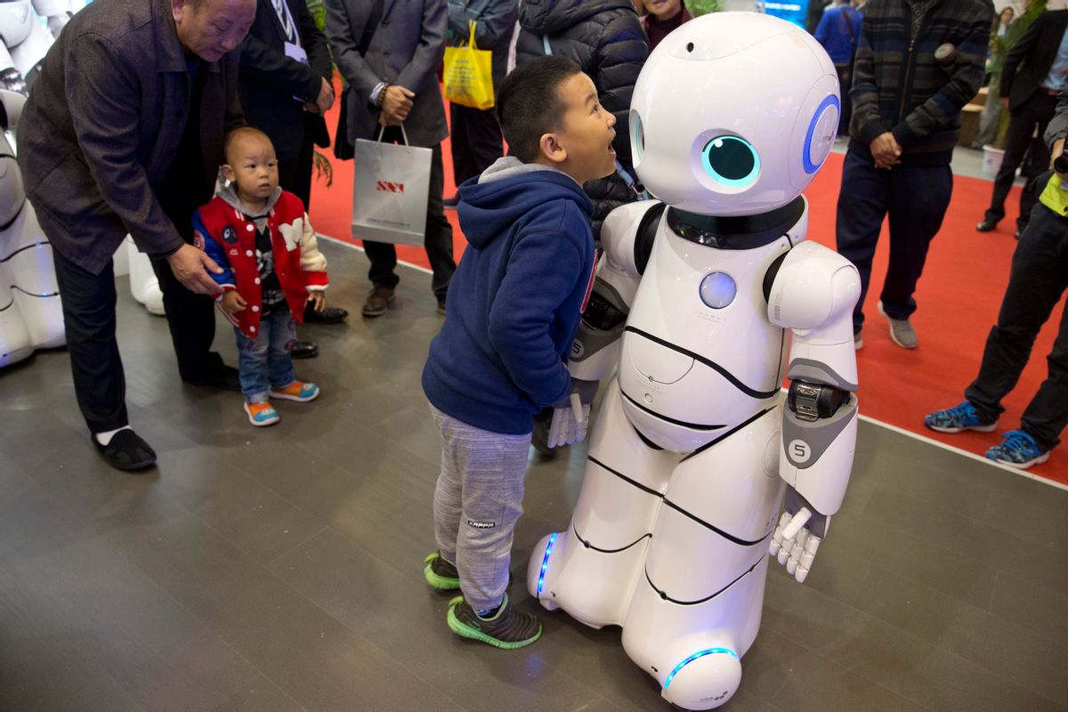 """In this Friday, Oct. 21, 2016 photo, a Chinese boy shouts into the Canbot, a companion robot, displayed during the World Robot Conference in Beijing, China. China is showcasing its burgeoning robot industry as it seeks to promote use of more advanced technologies in Chinese factories and create high-end products that redefine the meaning of """"Made in China."""" The Canbot can dance and respond to voice commands, while others can play badminton, sand cell phone cases and sort computer chips. (AP Photo/Ng Han Guan) (AP)"""