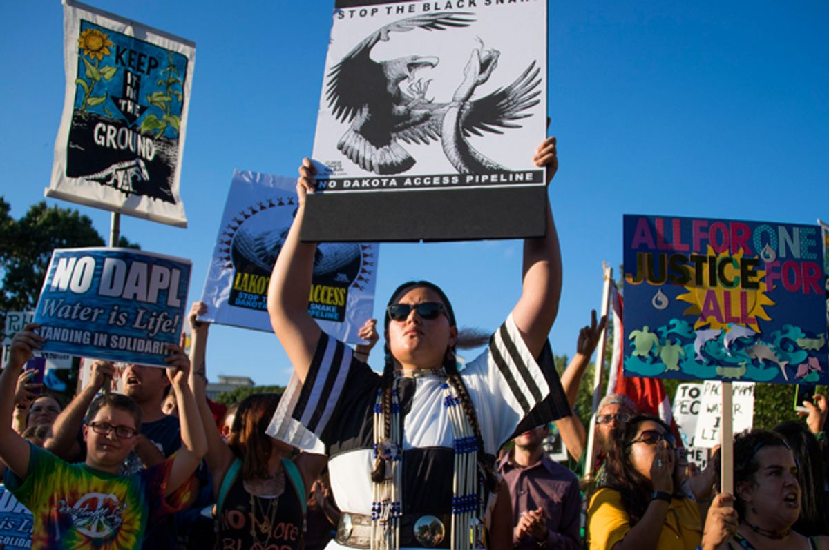 Demonstrators chant and hold up signs as they  protest the Dakota Access Pipeline   (Getty/Jim Watson)