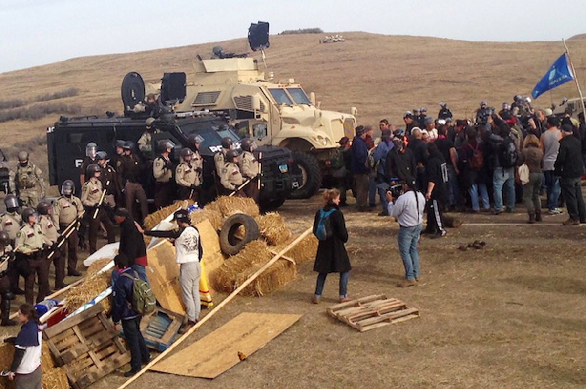 A line of police move towards a roadblock and encampment of Native American and environmental protesters near an oil pipeline construction site, near the town of Cannon Ball, North Dakota, U.S. October 27, 2016  (Reuters/Rob Wilson)