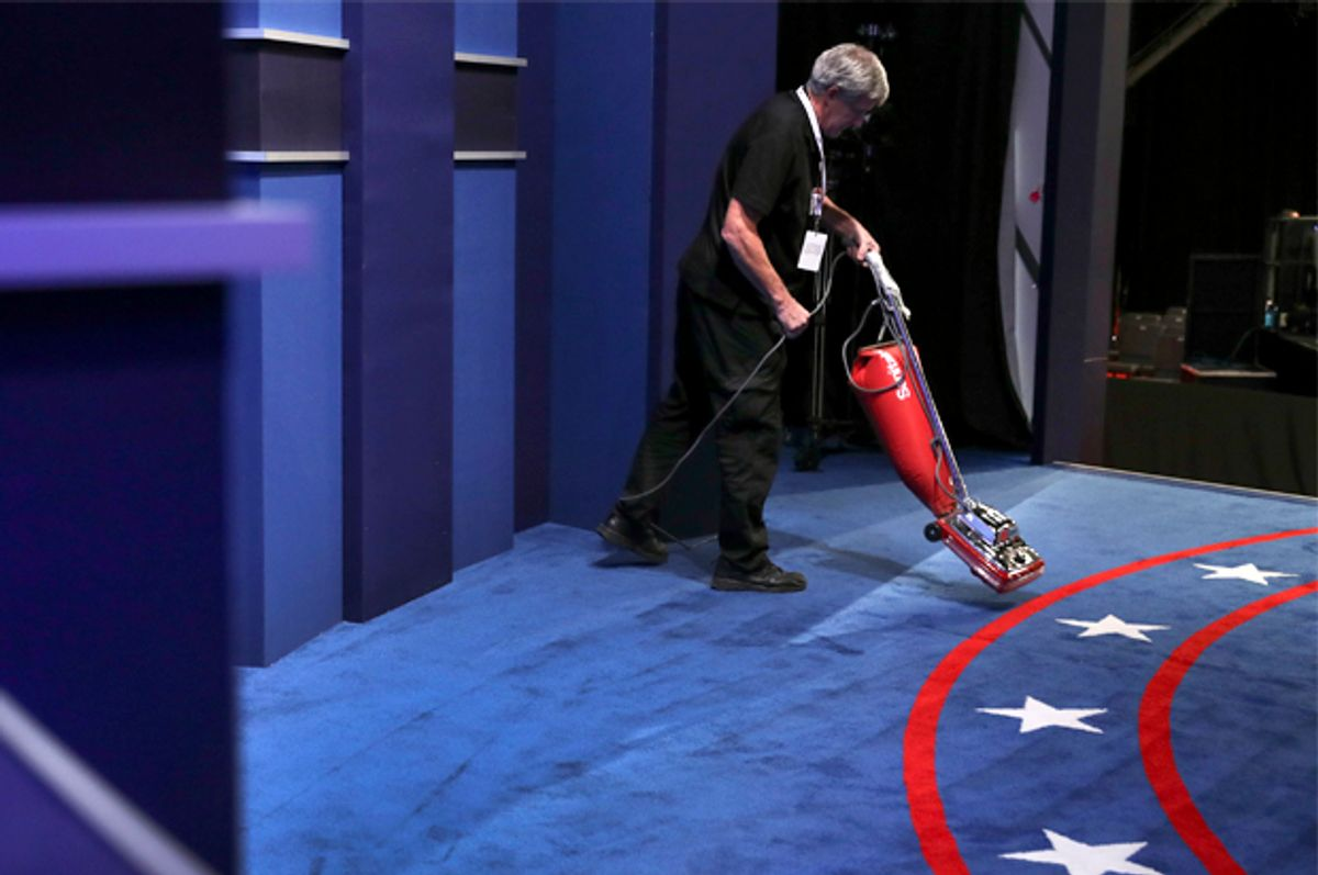 A stage hand vacuums the carpet before the third and final debate   (AP/Joe Raedle)