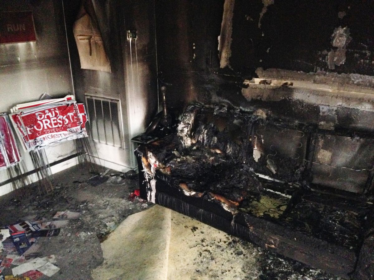 A burned couch is shown next to warped campaign signs at the Orange County Republican Headquarters in Hillsborough, NC on Sunday, Oct. 16 2016. (AP)