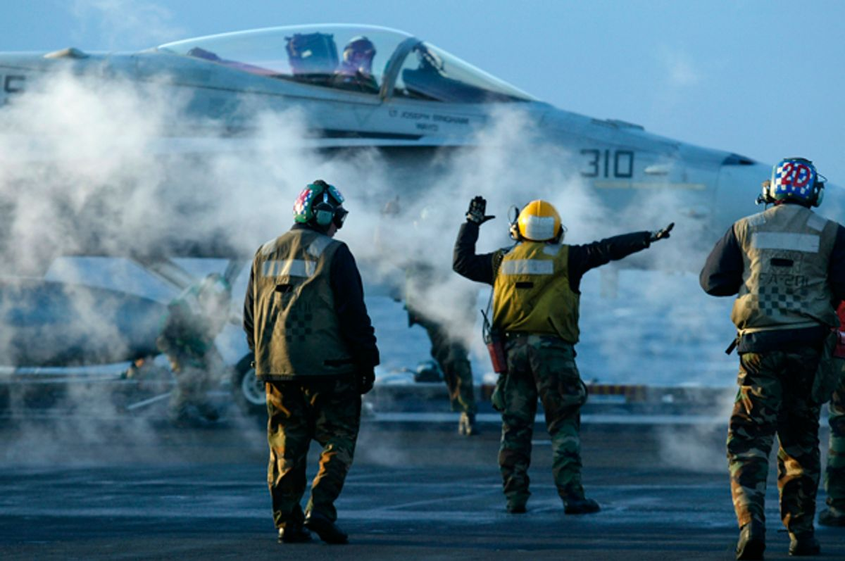 Flight deck crew prepare to launch an F/A 18 Hornet during early morning flight operations from the USS Theodore Roosevelt, Thursday March 20, 2003.   (AP/Richard Vogel)