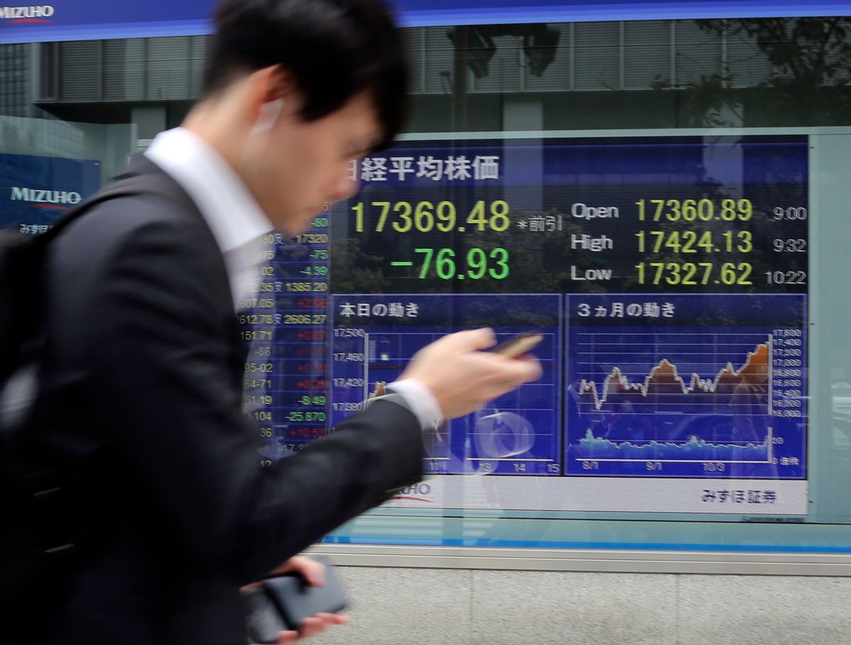 A man walks by an electronic stock board of a securities firm in Tokyo, Monday, Oct. 31, 2016. Asian stocks wobbled Monday as a revived FBI inquiry into U.S. presidential candidate Hillary Clinton's private email server sharpened uncertainty over the election, while investors also awaited key economic data this week. (AP Photo/Koji Sasahara) (AP)