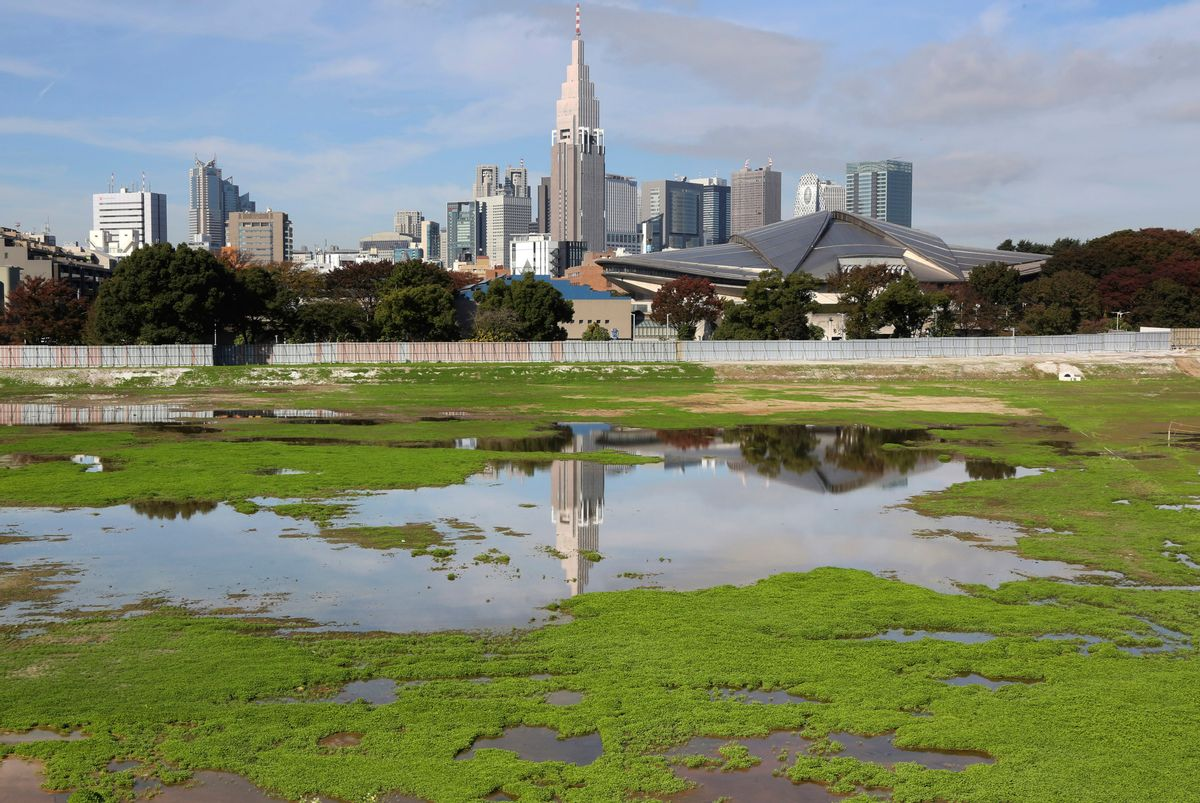 """FILE - In this Nov. 16, 2015, file photo, a skyscraper reflects in a pool of water in the site of Japan's National Stadium demolished for the renovation for the 2020 Olympic games as the compound is shown to the media for the first time after the completion of the demolition work in Tokyo. The price tag of the 2020 Tokyo Olympics could exceed 3 trillion yen ($30 billion) unless drastic cost-cutting measures are taken and several key venues are relocated, an expert panel warned Thursday, Sept. 30, 2016, in the latest blow to Japanese organizers. """"Naturally, anyone who hears these numbers is alarmed,"""" panel leader Shinichi Ueyama said. (AP Photo/Koji Sasahara, File) (AP)"""