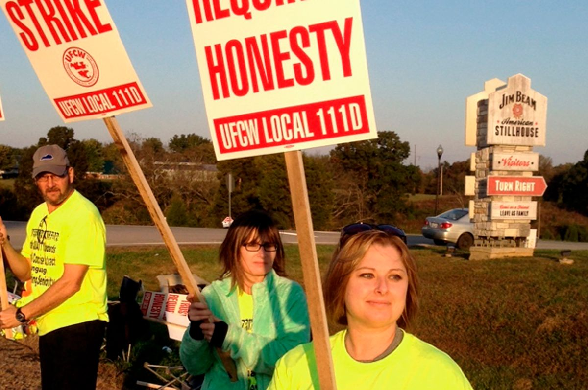 Workers hold picket signs outside the Jim Beam plant in Clermont, Ky.   (AP/Bruce Schreiner)
