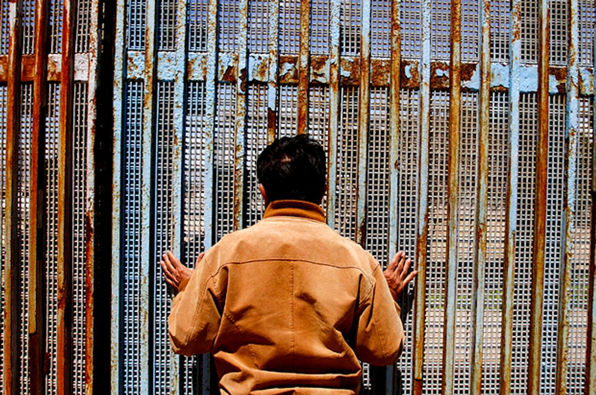 A man talks to a relative at a wall separating Mexico and the United States   (Reuters/Jorge Duenes)