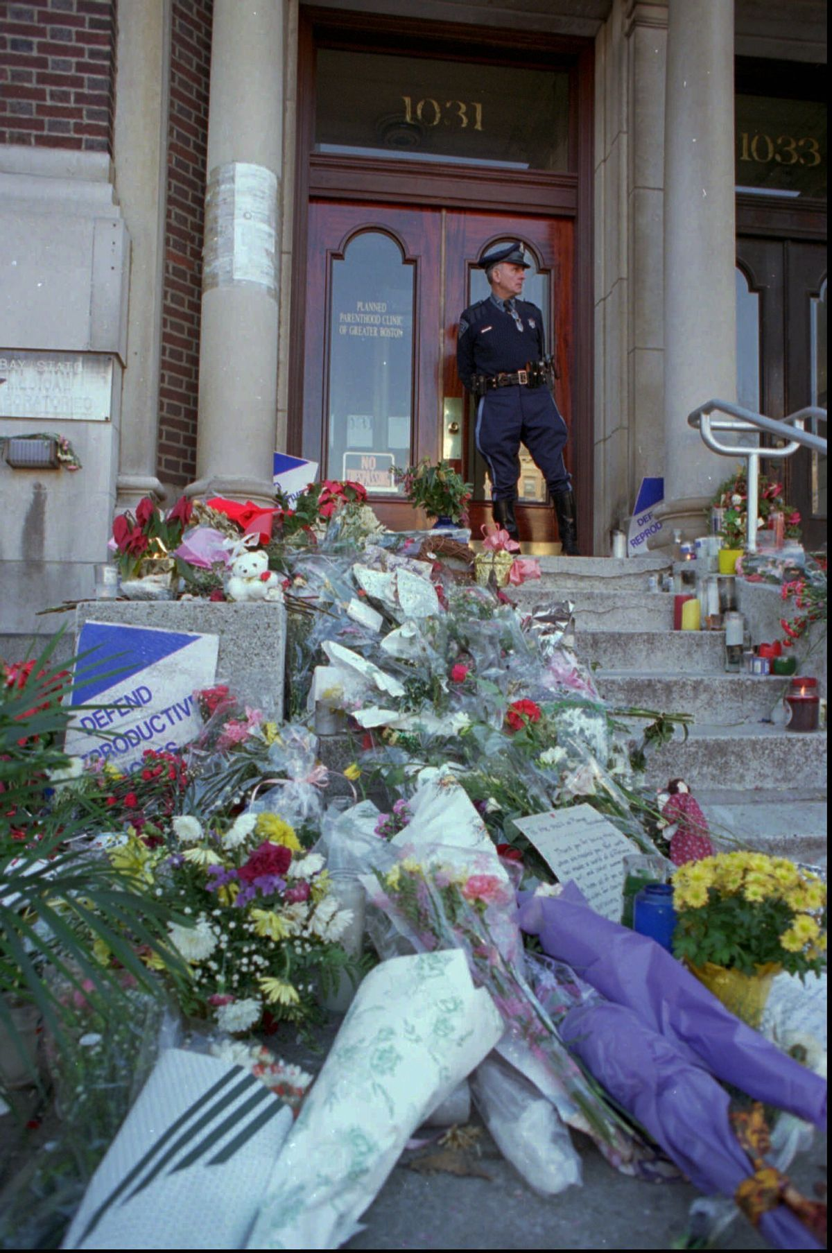 FILE - In this Wednesday, Jan. 4, 1995 file photo, Masssachusetts State Trooper Daniel Dhionis stands guard at the Planned Parenthood Clinic of Greater Boston in Brookline, Mass,, where flowers and letters were left after two women were killed, and five people injured in shootings at Planned Parenthood and another clinic. Planned Parenthood clinics have been repeated targets of bombings, arson and protests. (AP Photo/Julia Malakie) (AP)