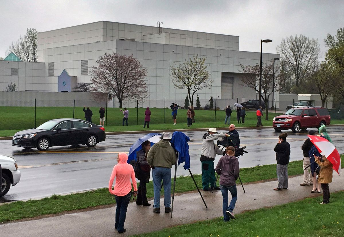 FILE - In this April 21, 2016, file photo, people stand outside the entertainer Prince's Paisley Park compound in Chanhassen, Minn. This week's public opening of Prince's suburban Minneapolis estate and studio complex likely will be delayed because the city council indefinitely postponed voting on a rezoning request for the complex to be operated as a museum. The Chanhassen City Council tabled the request Monday, Oct. 3. Paisley Park tours were due to begin Thursday, Oct. 6. (Jim Gehrz/Star Tribune via AP, File) (AP)