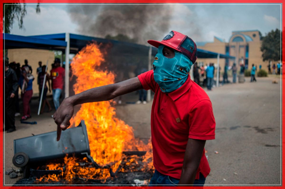 TOPSHOT - Students from Vaal University of Technology (VUT) shout slogans next to a burning barricade during clashes with South African anti-riot police and campus security at a demonstration in support of the Fees Must Fall Movement in Vanderbijlpark on October 13, 2016. Weeks of protests at South African universities have targeted tuition fees. / AFP / MUJAHID SAFODIEN        (Photo credit should read MUJAHID SAFODIEN/AFP/Getty Images) (Afp/getty Images)