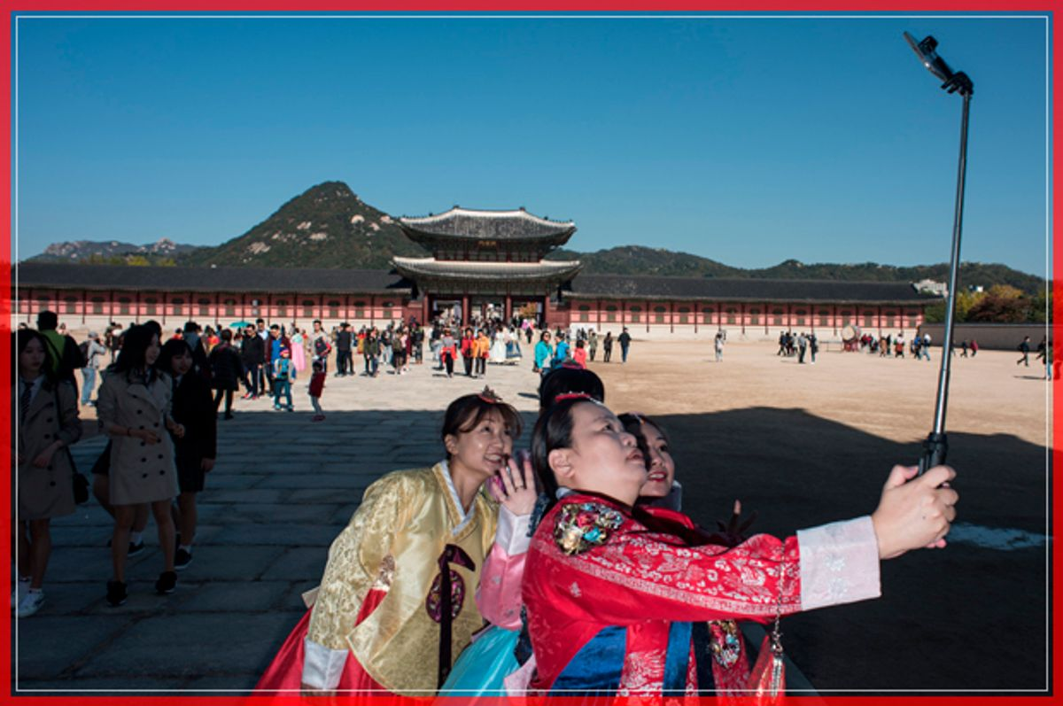Tourists take photos as they visit Gyeongbokgung palace in Seoul on October 24, 2016. / AFP / Ed Jones        (Photo credit should read ED JONES/AFP/Getty Images) (Afp/getty Images)