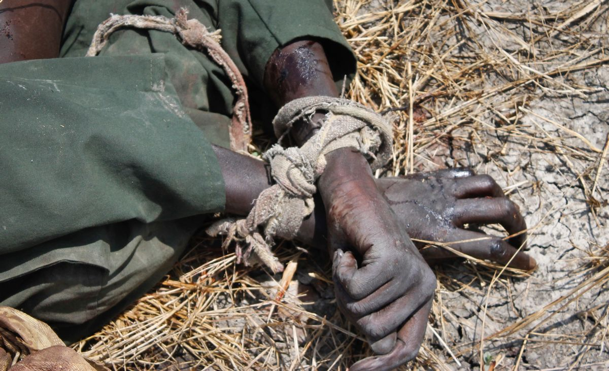 In this photo taken Sunday, Oct. 16, 2016, the body of a rebel soldier who died in a battle days before is seen with his hands tied, in Malakal, South Sudan. Following clashes last week in the outskirts of the city, which has been reduced to rubble and almost entirely deserted by civilians, the army flew in journalists on Sunday to show that they retain control of the strategic city, even though rebels still vow to take it. (AP Photo/Justin Lynch) (AP)