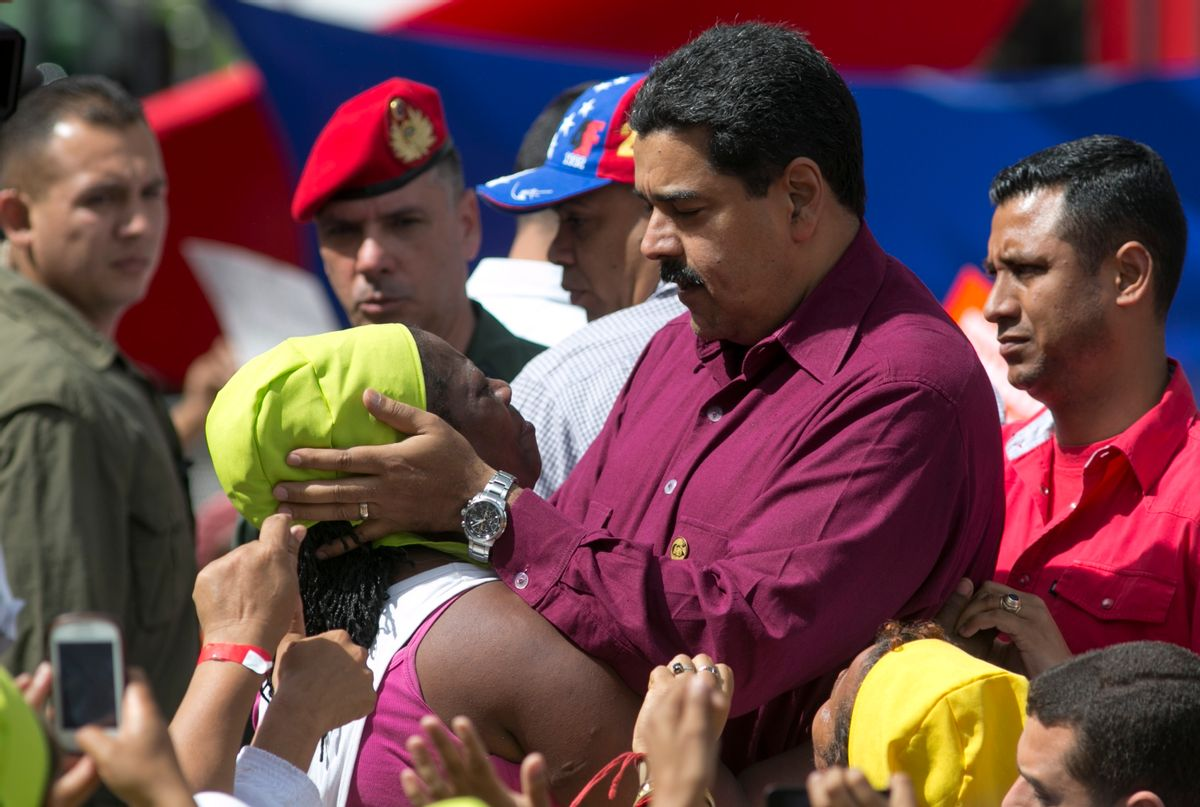 Venezuela's President Nicolas Maduro listens to a supporter during a rally outside Miraflores presidential palace in Caracas, Venezuela, Friday, Oct. 28, 2016. For the most part, residents of Venezuela's capital ignored calls to stay home Friday to protest Maduro, handing a rare victory to the embattled leader. (AP Photo/Ariana Cubillos) (AP)