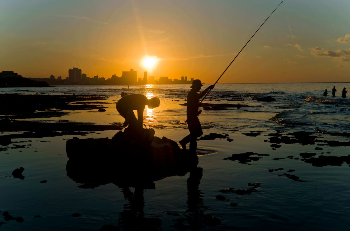In this Nov. 11, 2016 photo, fishermen throw their fishing rods from Chivo beach as the sun sets in Havana, Cuba. Cuba has been renowned for its fishing at least since the days of Ernest Hemingway, and foreigners by the thousands come each year to fish in waters largely protected by Cuba's lack of development. () (AP Photo/Ramon Espinosa)