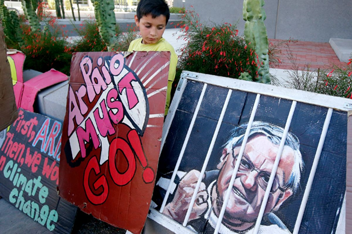 A protester stands with his sign during a rally in front of the Maricopa County Sheriff's Office Headquarters   (AP/Ross D. Franklin)