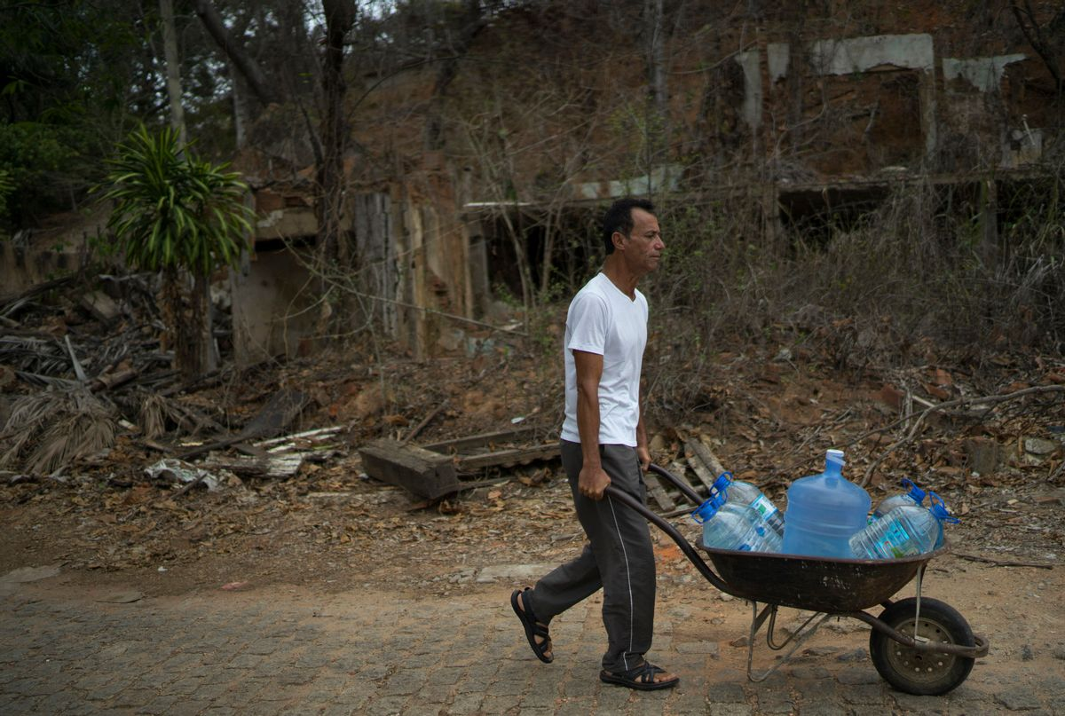 """In this Oct. 11, 2016 photo, Lazimar Caliari pushes a wheelbarrow loaded with gallons of well water, in Colatina, Brazil. The 53-year-old musician is concerned about the quality of the water in the Doce River a year after a dam of mine waste broke, sending metal-laden mud into the Doce. """"The mayor doesn't drink the water form the Doce River, so why should I have to drink it too?"""" asks Caliari. (AP Photo/Leo Correa) (AP)"""