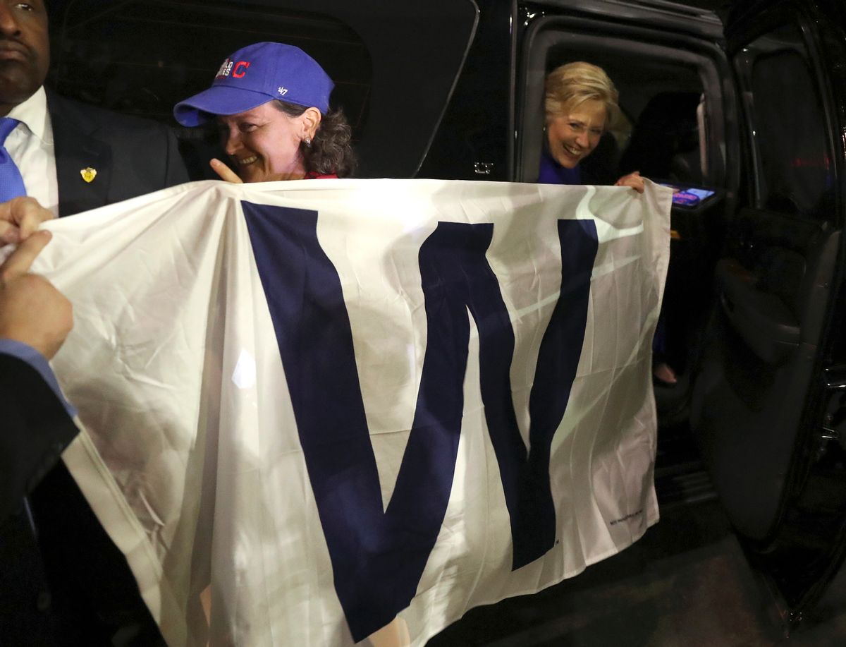 Democratic presidential candidate Hillary Clinton holds a 'W' banner as the Chicago Cubs win the World Series baseball Game 7 against the Cleveland Indians after her final campaign rally of the day at Arizona State University in Tempe, Ariz., Wednesday, Nov. 2, 2016. (AP Photo/Andrew Harnik) (AP)
