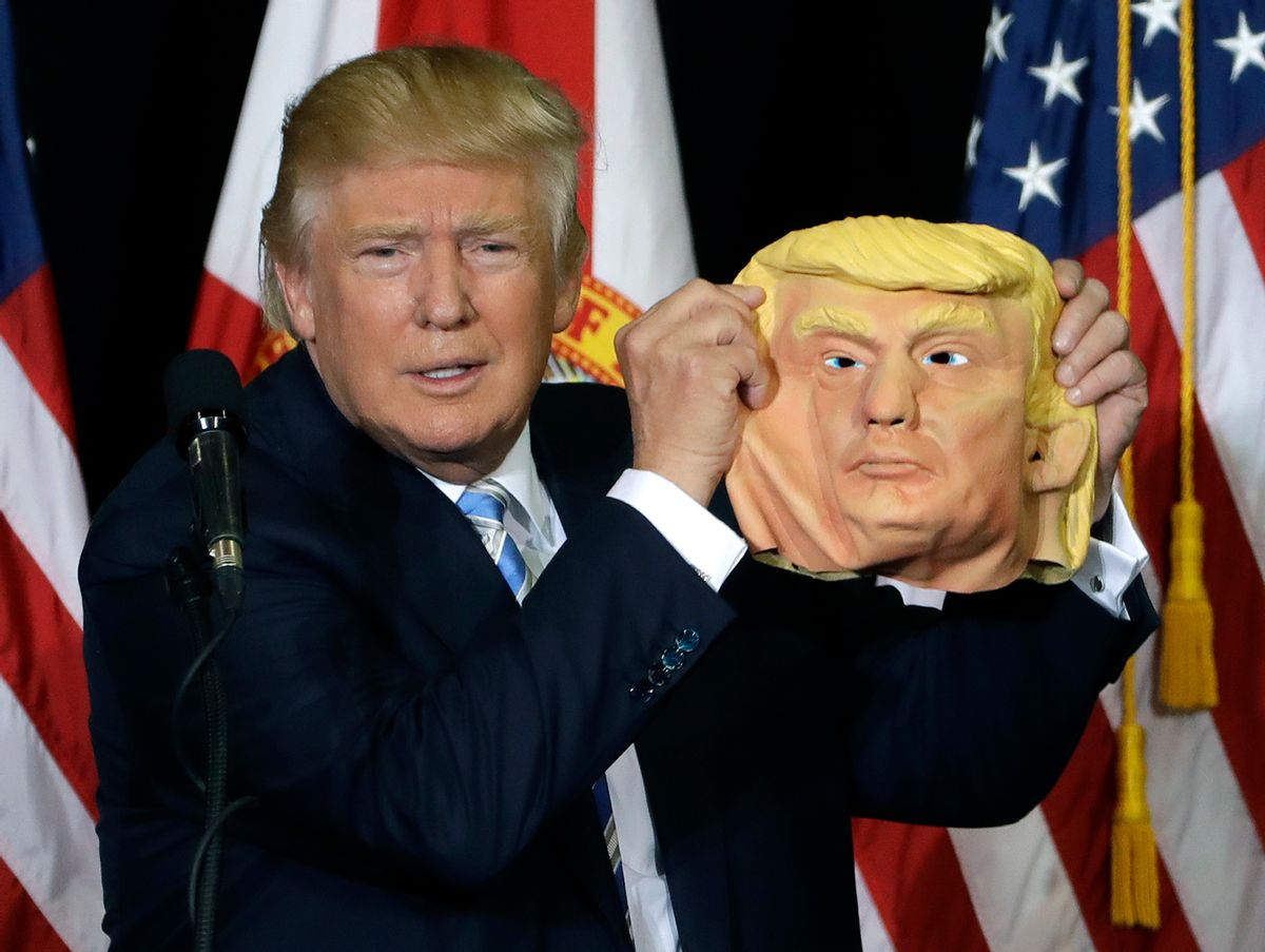 Republican presidential candidate Donald Trump holds up a Donald Trump mask during a campaign speech, Monday, Nov. 7, 2016, in Sarasota, Fla.  (AP)