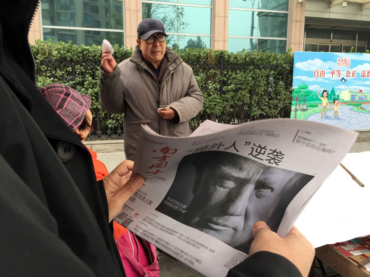 """A Chinese man holds up a Chinese newspaper with the front page photo of U.S. President-elect Donald Trump and the headline """"Outsider counter attack"""" at a newsstand in Beijing, China, Thursday, Nov. 10, 2016. Trump is a mixed blessing for Chinese leaders. His threats to tear up trade deals and hike tariffs on Chinese goods could chill thriving commercial ties when Beijing is struggling to shore up economic growth. At the same time, Trump's suggestion he might reduce Washington's global strategic presence to focus on domestic issues would be a gift to Chinese leaders. They could expand their political and military profile in East Asia with less risk of conflict. () (AP Photo/Ng Han Guan)"""