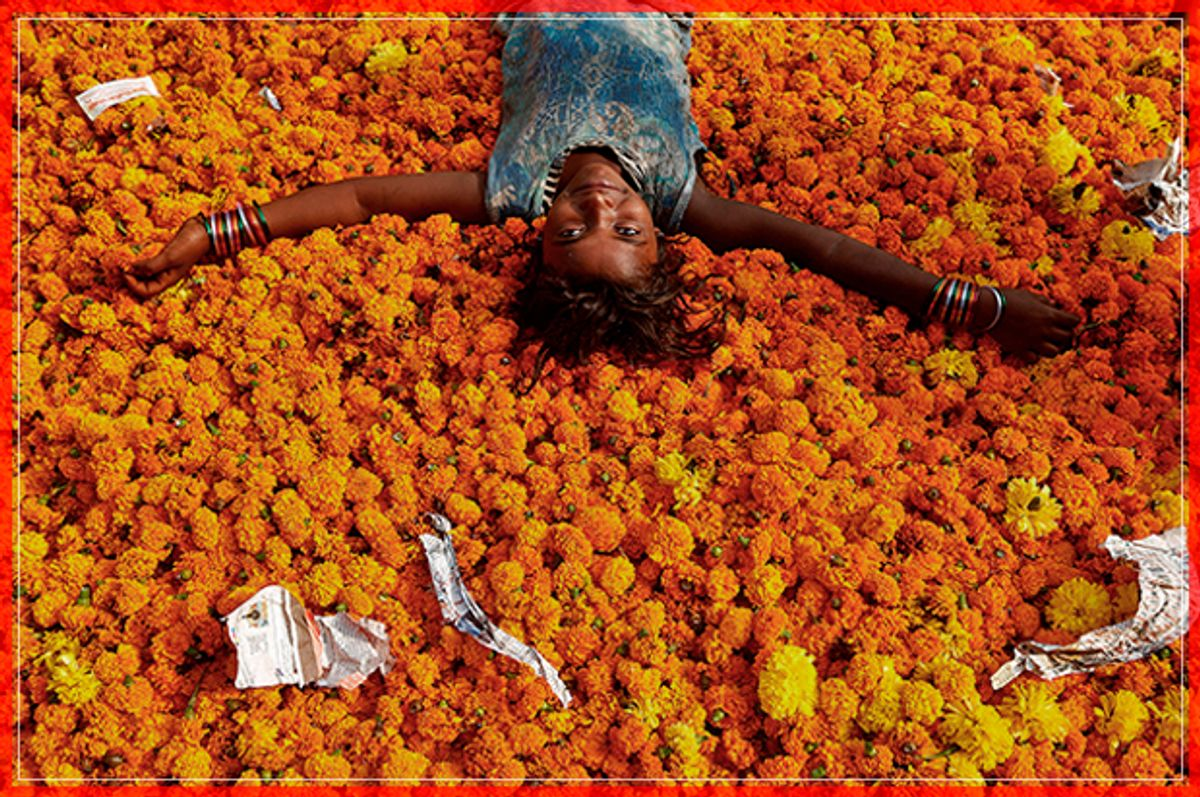 A girl plays on a pile of discarded flowers outside a market, the day after the Diwali celebrations in Mumbai, India October 31, 2016. REUTERS/Shailesh Andrade - RTX2R7MP (Reuters)