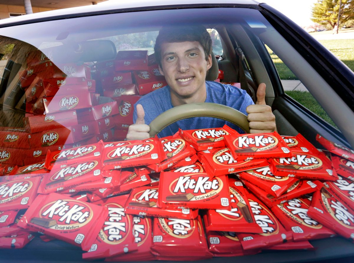 """In this Nov. 3, 2016, photo Hunter Jobbins, freshman at Kansas State University, poses in his car filled with nearly 6,500 Kit Kat bars in Manhattan, Kansas. Jobbins told The Wichita Eagle he left his car unlocked with a Kit Kat in the cupholder last month before running into his dorm building. When he came back, the candy bar had been replaced with a note. The thief wrote, """"I love Kit Kats so I checked your door and it was unlocked. Did not take anything other than the Kit Kat. I am sorry and hungry."""" Jobbins' picture of the note went viral on Twitter and Hershey responded by sending a representative to the campus with 6,500 Kit Kat bars. (Colin E. Braley/AP Images for The Hershey Company) (AP)"""