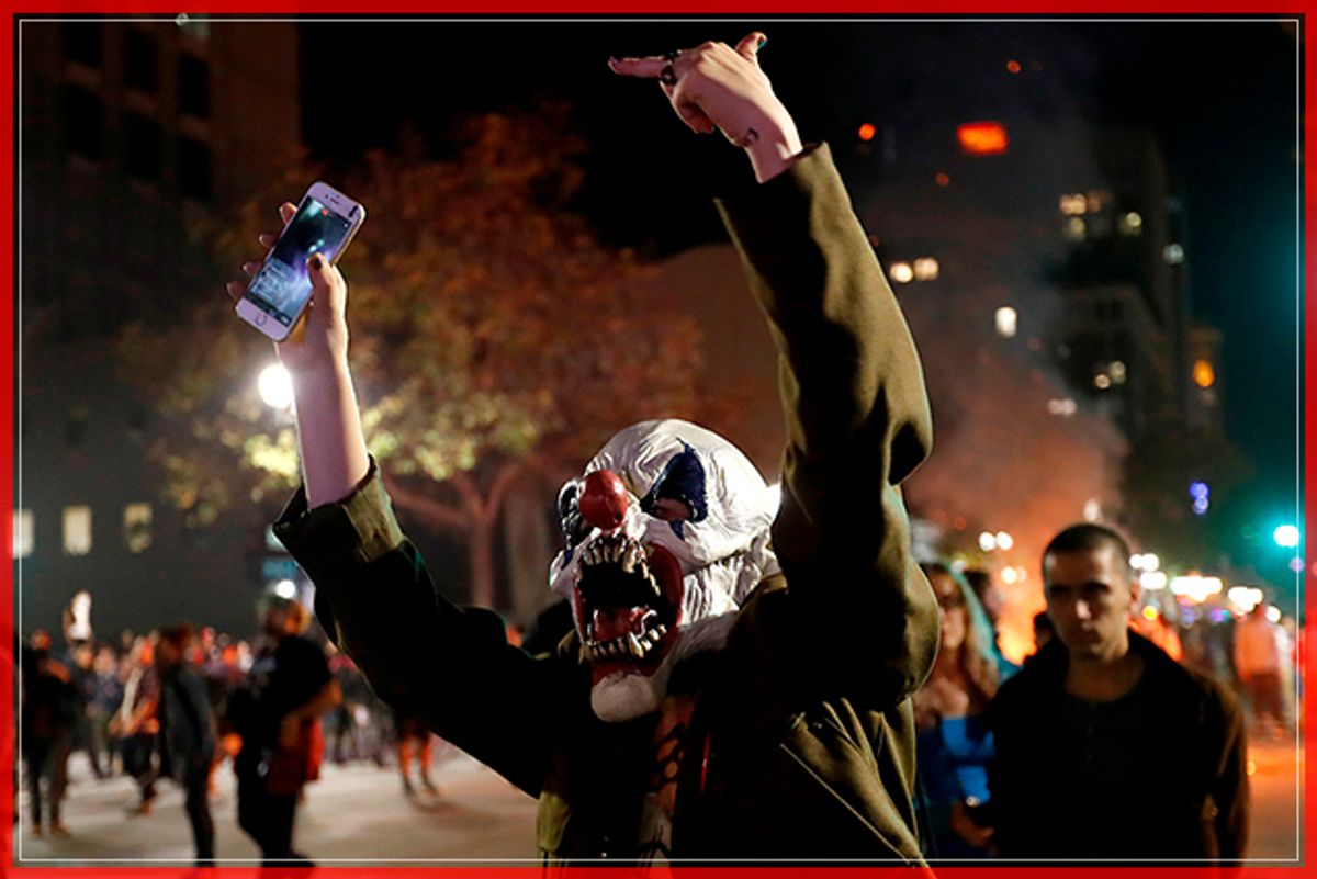 A masked demonstrator gestures toward a police line during a demonstration in Oakland, California, U.S. following the election of Donald Trump as President of the United States November 9, 2016. REUTERS/Stephen Lam - RTX2SXVM (Reuters)