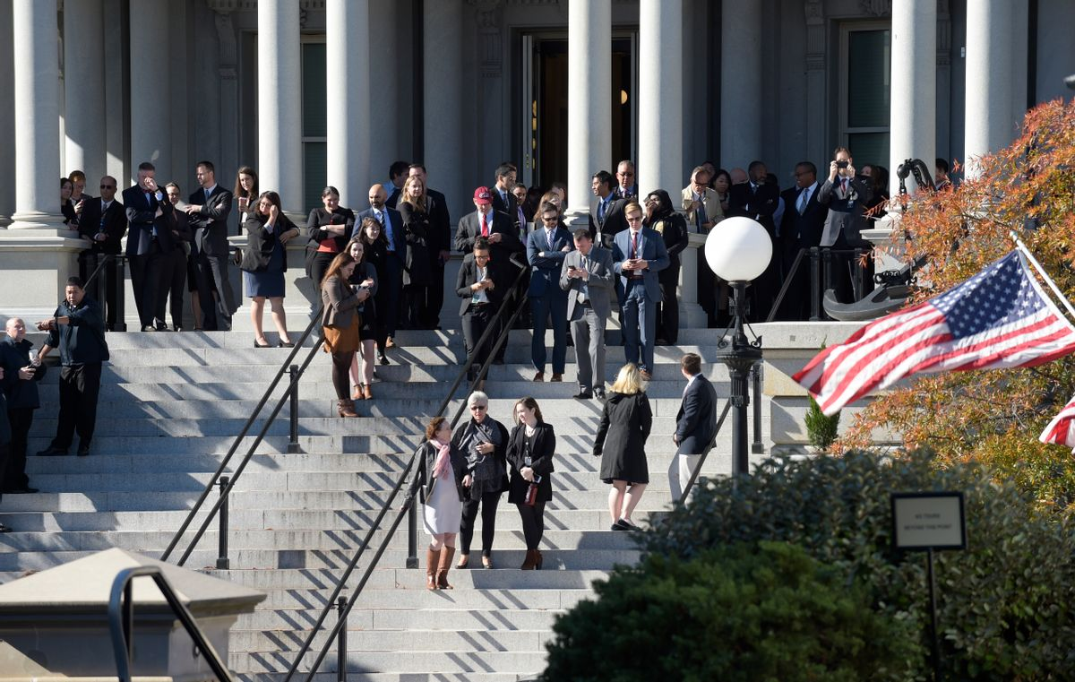 People stand on the steps of the Eisenhower Executive Office Building, next to the White House in Washington, Thursday, Nov. 10, 2016, as they wait for the arrival of President-elect Donald Trump for his meeting with President Barack Obama. (AP Photo/Susan Walsh) (AP)