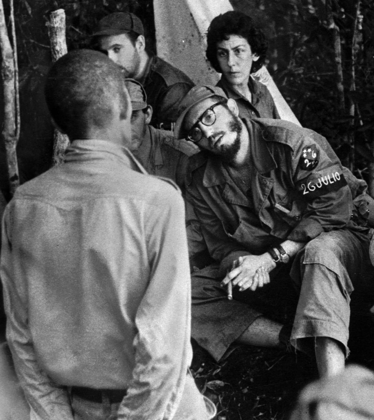 FILE - In this 1958 file photo, Cuba's leader Fidel Castro, center, questions a man charged with banditry as Celia Sanchez looks on during a trial held in the guerrillas' base in the Cuban mountain range of Sierra Maestra.  (AP)