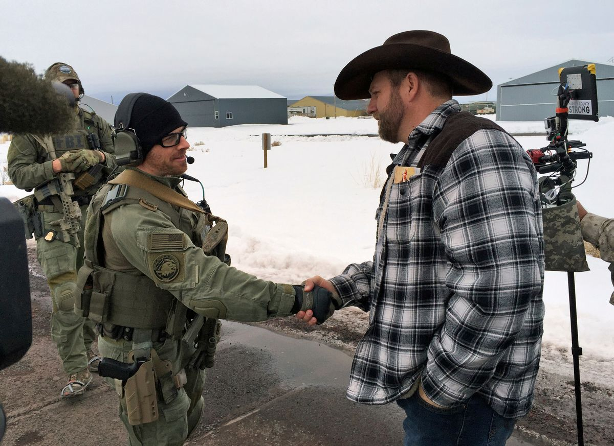 """FILE - In this Jan. 22, 2016, file photo, Ammon Bundy, right, shakes hand with a federal agent guarding the gate at the Burns Municipal Airport in Burns, Ore. Bundy, the leader of a federal wildlife refuge takeover in Oregon says his group will """"continue to stand"""" after he and six others were acquitted last week in Portland, Ore., of charges in the case. Bundy remains in jail because he still faces charges in the 2014 standoff at his father's Nevada ranch. (AP Photo/Keith Ridler, File) (AP)"""