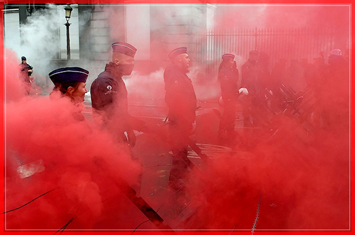 Belgian police officers stand guard amid red smoke after protesters threw coloured smoke grenades during a demonstration in Brussels organised by the Belgian military unions to protest against a decision by the government to raise the retirement age for soldiers to 63 on November 15, 2016. / AFP / JOHN THYS        (Photo credit should read JOHN THYS/AFP/Getty Images) (Afp/getty Images)